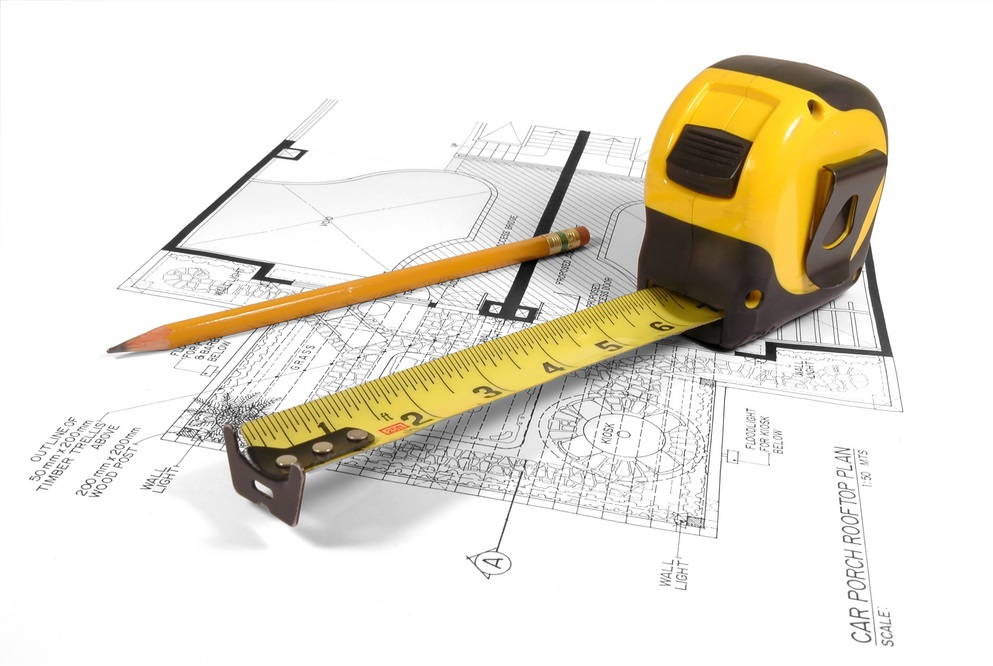 Tape Measure and Pencil on top of a Floor Plan