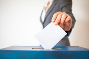 Image of a ballot box and vote being cast